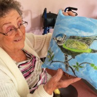A Trowbridge group member with their painted silk cushion